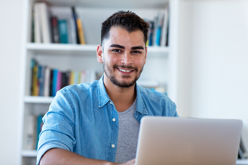 1127582480 istock photo Laughing mexican hipster man at work with laptop 1127581005