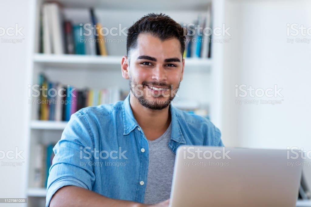 Risa a hombre hipster mexicano en el trabajo con ordenador portátil - foto de stock