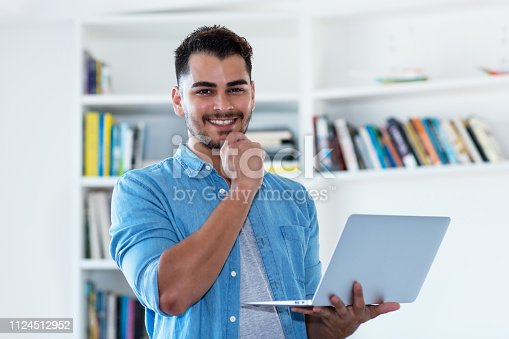 1127582480istockphoto Laughing mexican hipster man with beard and computer 1124512952