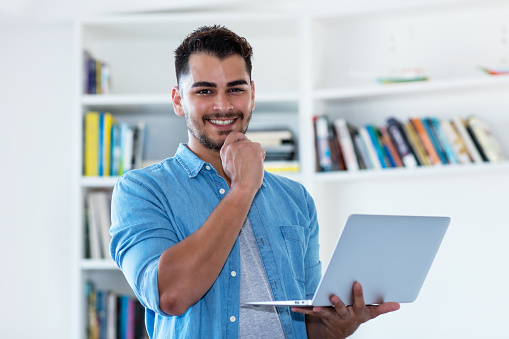 1127582480 istock photo Laughing mexican hipster man with beard and computer 1124512952