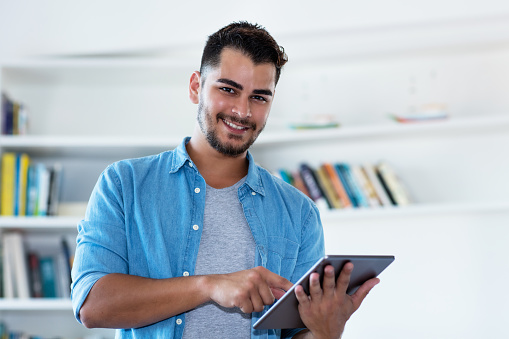 istock Laughing mexican hipster man with beard and tablet 1124515103
