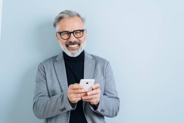 Laughing middle-aged man with smartphone Bearded middle-aged man with grey hair, holding smartphone, looking at camera and laughing. Half-length front portrait against blue wall background with copy space only mature men stock pictures, royalty-free photos & images