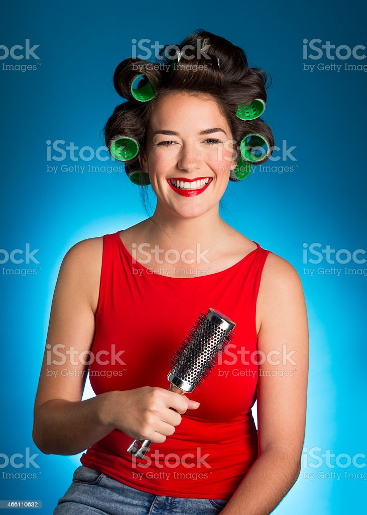 Fashion model laughing while getting her hair and makeup done.