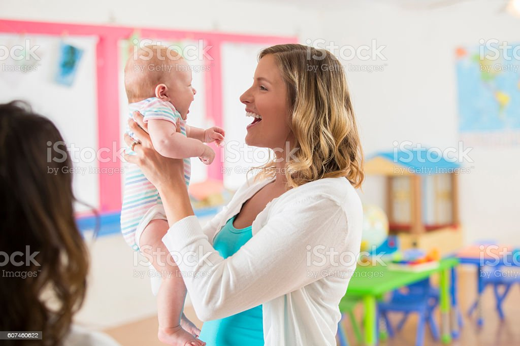 Laughing mother holding her sweet infant baby girl in daycare stock photo