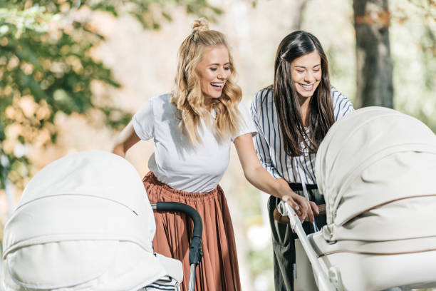 laughing mothers looking in baby stroller in park laughing mothers looking in baby stroller in park baby carriage stock pictures, royalty-free photos & images
