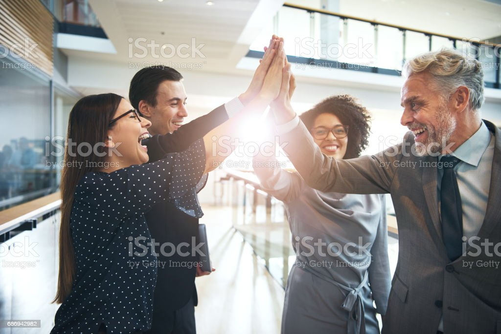 Laughing multiethnic team giving high five in office foto stock royalty-free