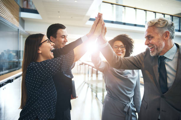 Laughing multiethnic team giving high five in office - foto stock