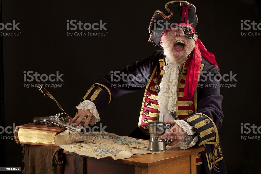 Laughing old pirate captain with treasure map holds pewter mug stock photo