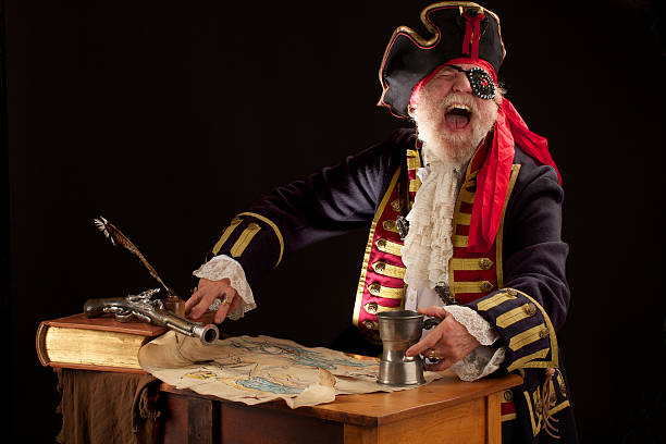 laughing old pirate captain with treasure map holds pewter mug - pirates stock photos and pictures