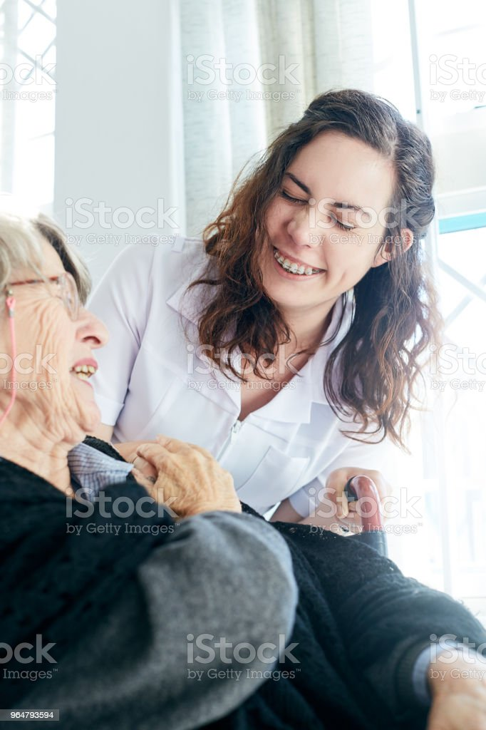 Laughing old woman and nurse share a joke royalty-free stock photo