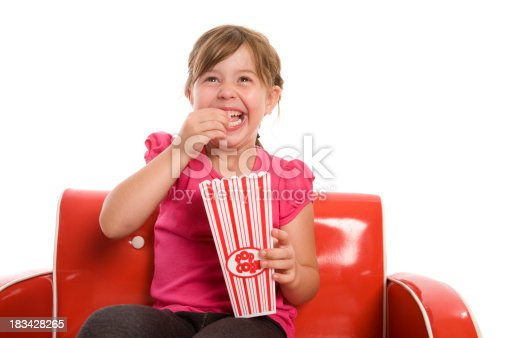 A little girl enjoying her popcorn and a movie isolated on white.