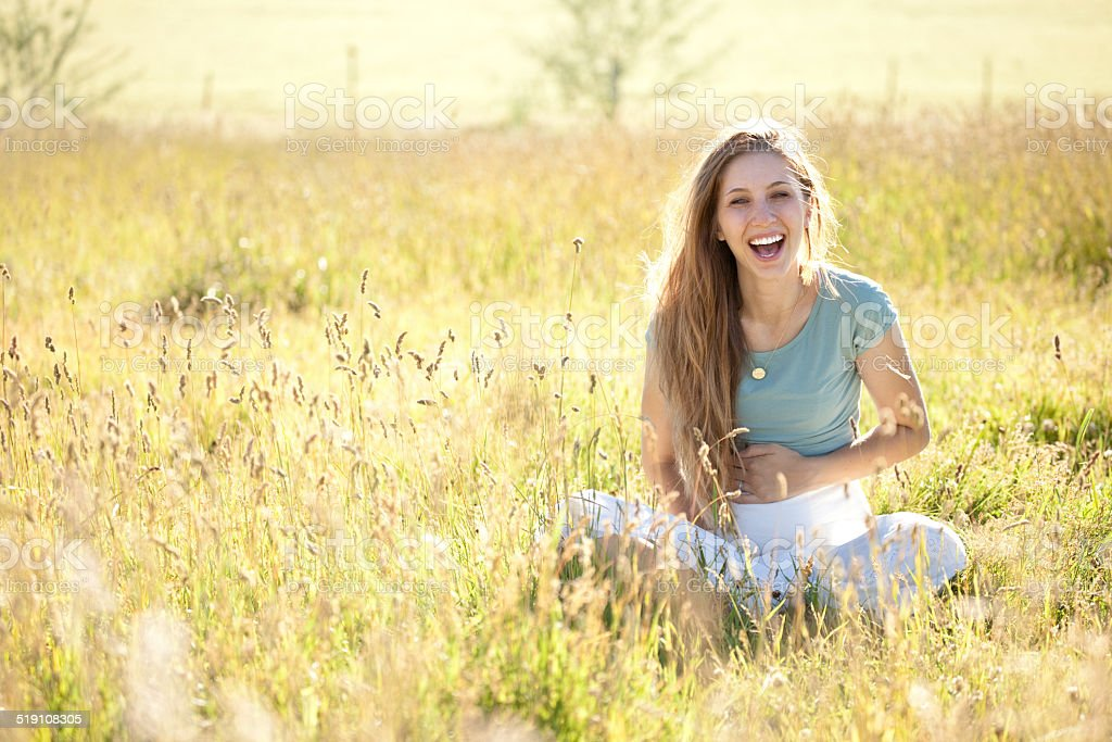 Laughing Pregnant Woman Sitting in Sunshine and Meadow stock photo