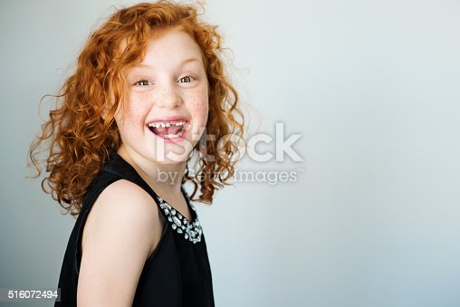 istock Laughing redhead little girl with freckles and missing tooth. 516072494