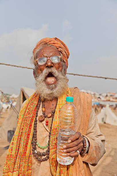 Laughing Sadhu with water bottle stock photo