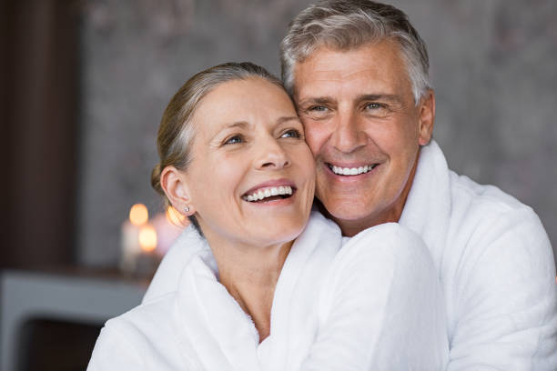 Laughing senior couple embracing at spa Smiling husband embracing cheerful wife from behind at spa. Laughing mature couple enjoying a romantic hug at wellness center after massage. Senior man and woman in white in bathrobe relaxing at spa. mature couple stock pictures, royalty-free photos & images