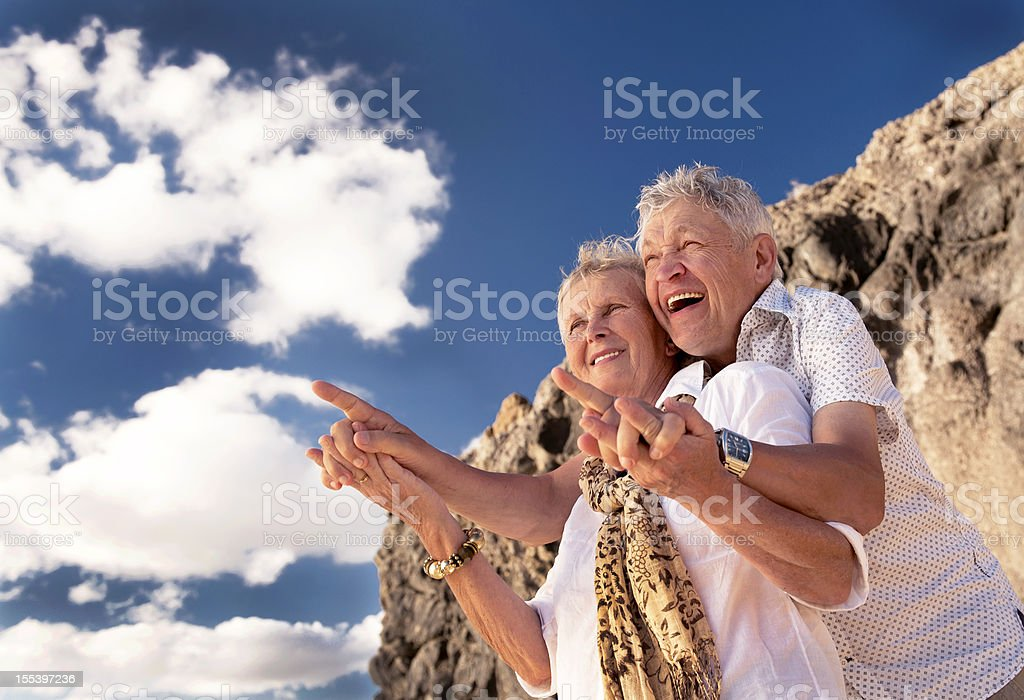 Laughing senior couple pointing against blue sky stock photo