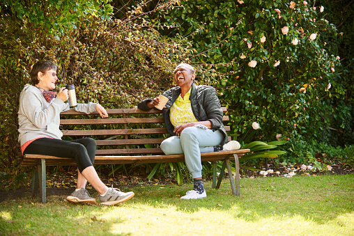 Two senior female friends talking and laughing together over coffees while social distancing on a park bench
