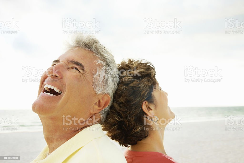 Laughing senior man and woman with heads together on beach royalty-free stock photo