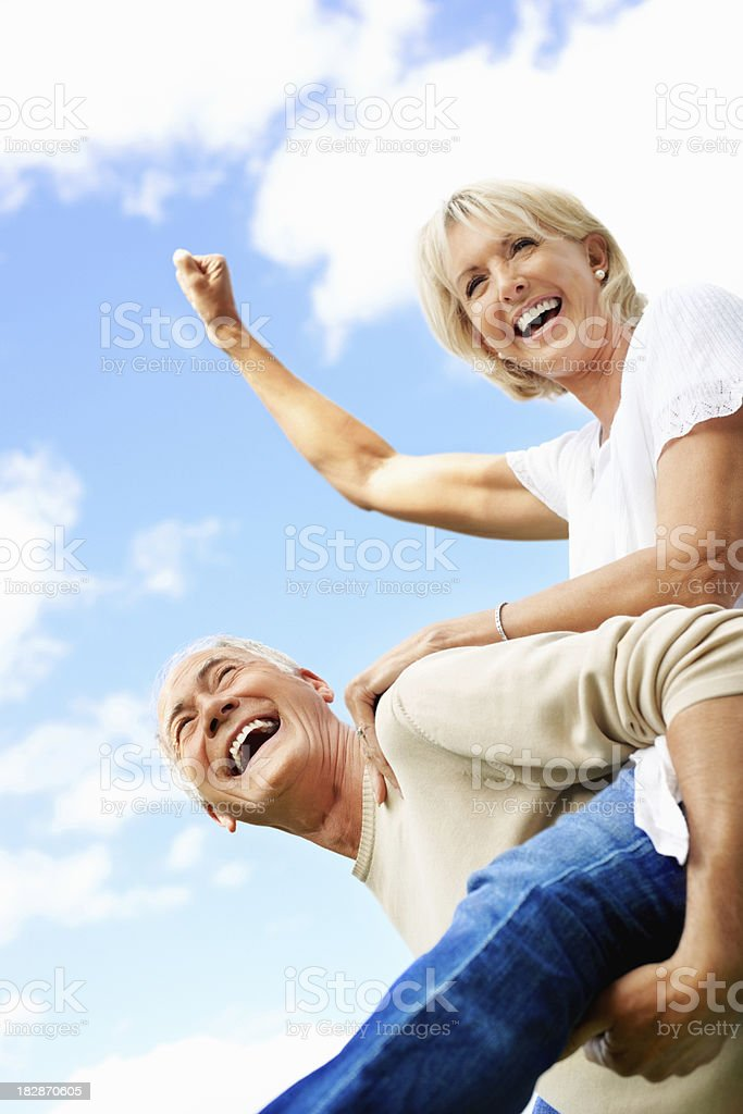 Laughing senior man piggybacking a mature woman against cloudy sky royalty-free stock photo