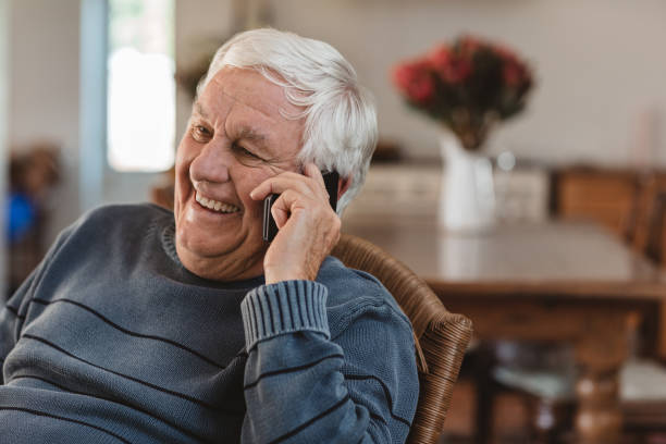 Laughing senior man talking on a cellphone in at home stock photo
