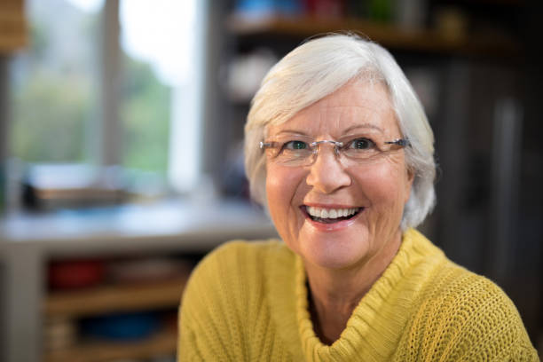 Laughing senior woman in the kitchen Portrait of laughing senior woman in the kitchen 65 69 years stock pictures, royalty-free photos & images