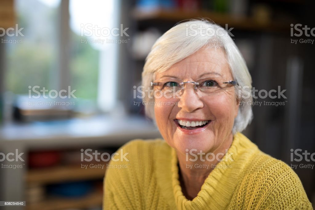 Laughing senior woman in the kitchen stock photo