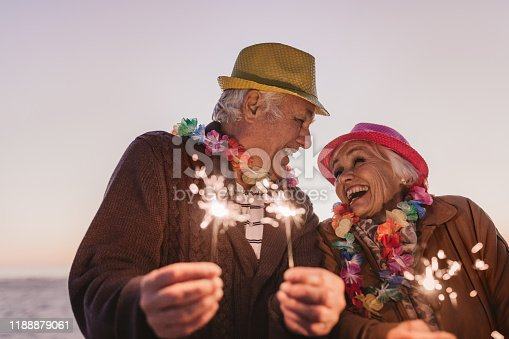 Laughing senior couple dressed in party hats and holding sparklers while celebrating New Year's Eve together at the beach at sunset