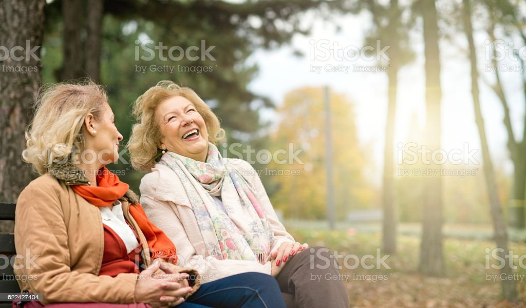 Laughing seniors. Two laughing senior friend relaxing at the park 50-59 Years Stock Photo