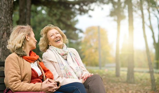 Two laughing senior friend relaxing at the park