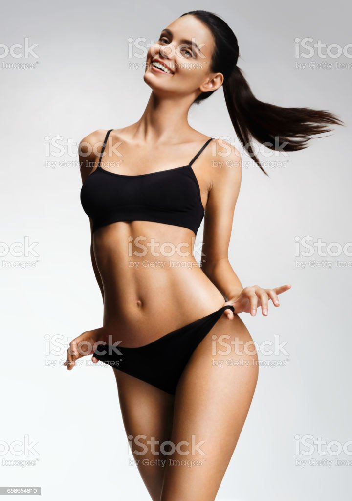 Laughing sexy girl in black bikini posing on grey background. stock photo