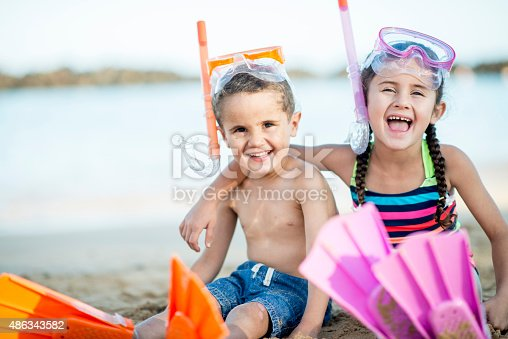 605742160 istock photo Laughing Siblings on the Beach 486343582