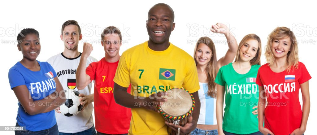 Laughing soccer supporter with drum and fans from other countries royalty-free stock photo