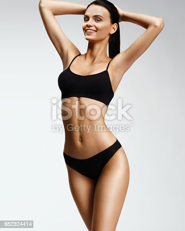 676005390istockphoto Laughing sporty girl in black bikini posing on grey background 652324414