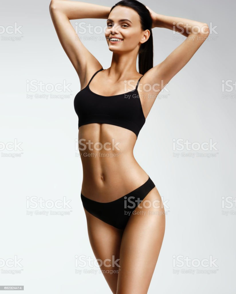 Laughing sporty girl in black bikini posing on grey background stock photo