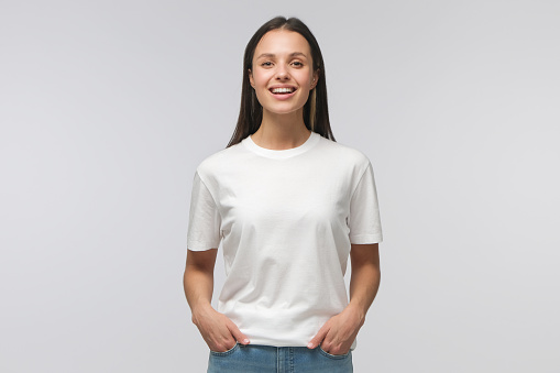 istock Laughing student girl wearing white T-shirt and blue jeans, standing with hands in pockets, looking straight at camera, isolated on gray background 1217002161