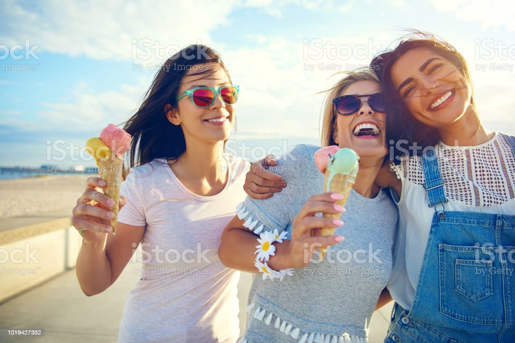 Laughing teenage girls enjoying ice cream cones - Foto stock royalty-free di Abbracciare una persona