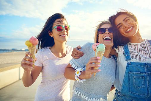 Laughing Teenage Girls Enjoying Ice Cream Cones - Fotografie stock e altre immagini di Abbracciare una persona