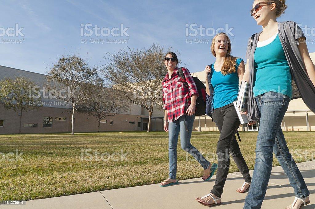 Laughing Teenage Girls Walking with School Building in Background stok fotoğrafı