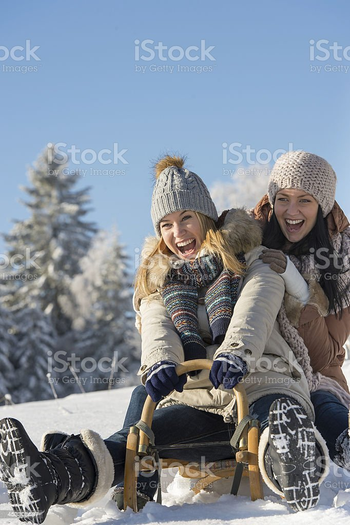 Laughing teenagers sledge downhill in wintertime stock photo