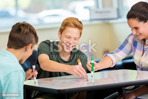 istock Laughing teenagers working at makerspace on animation project 604355606