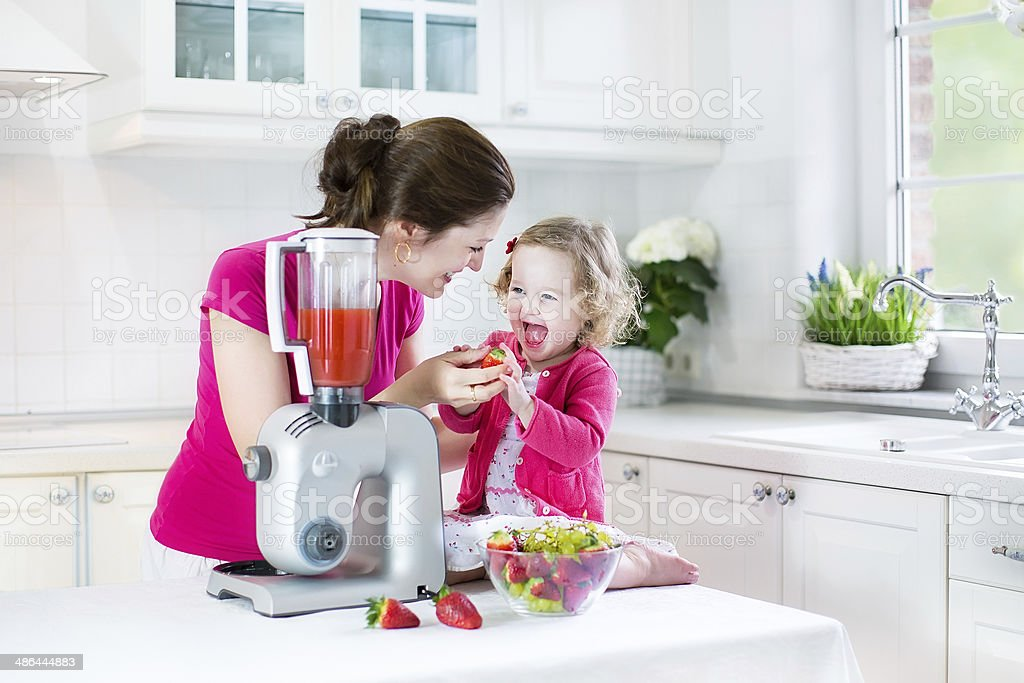 Laughing toddler girl and beautiful mother in sunny white kitchen stock photo