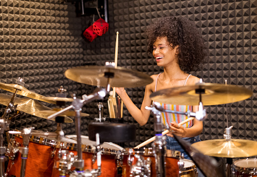 Laughing happy vivacious young Afro American woman in her twenties seated playing drums and cymbals in a studio