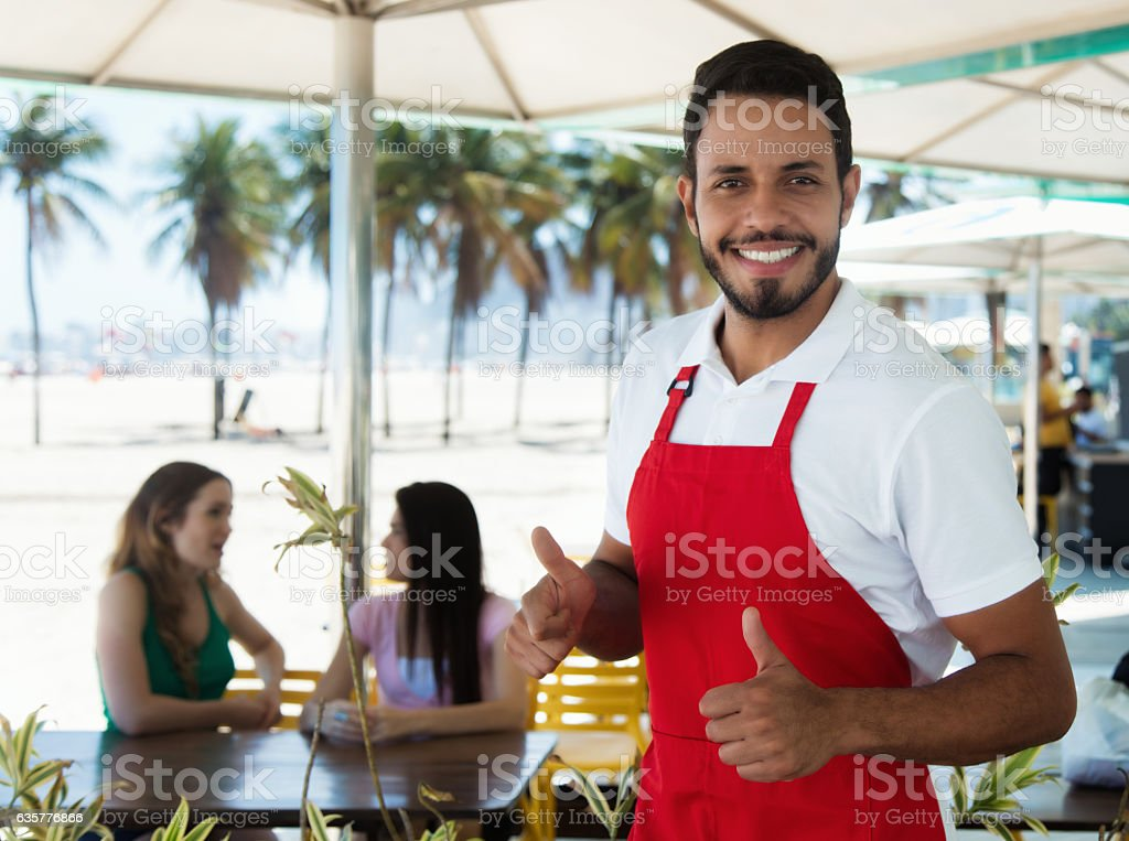 Laughing waiter of a cocktail bar at beach stock photo