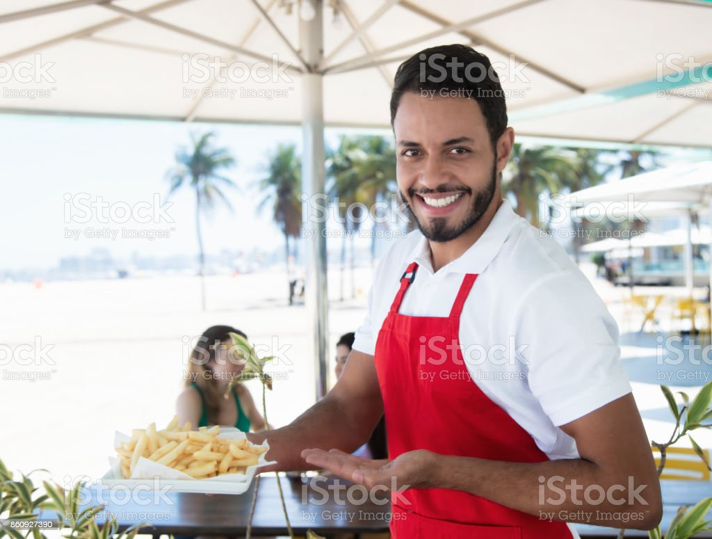 Risa de camarero sirviendo patatas fritas en el bar de la playa - foto de stock