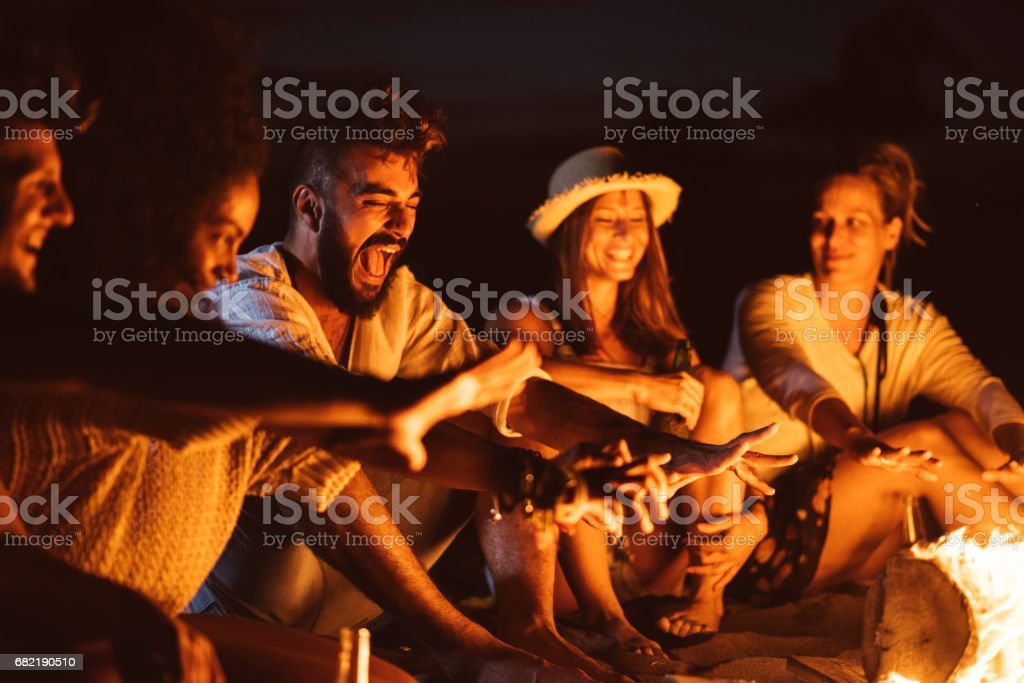 Laughing with friends at the beach stock photo