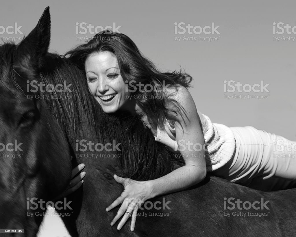 laughing woman and stallion stock photo