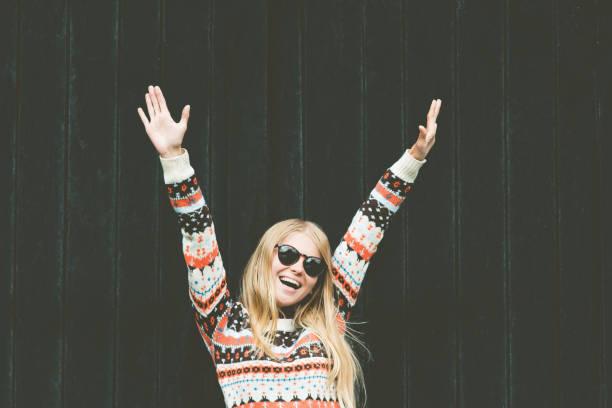 Lachende Frau glücklich Hände hoch erhobenen Wellness Lifestyle emotionale mädchenmode mit gemütlichen Pullover auf hölzernen schwarzen Hintergrund – Foto