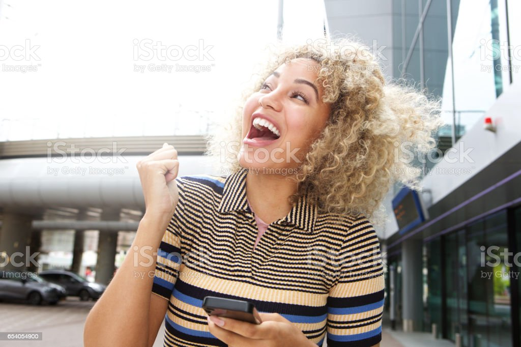 Laughing woman holding cellphone stock photo