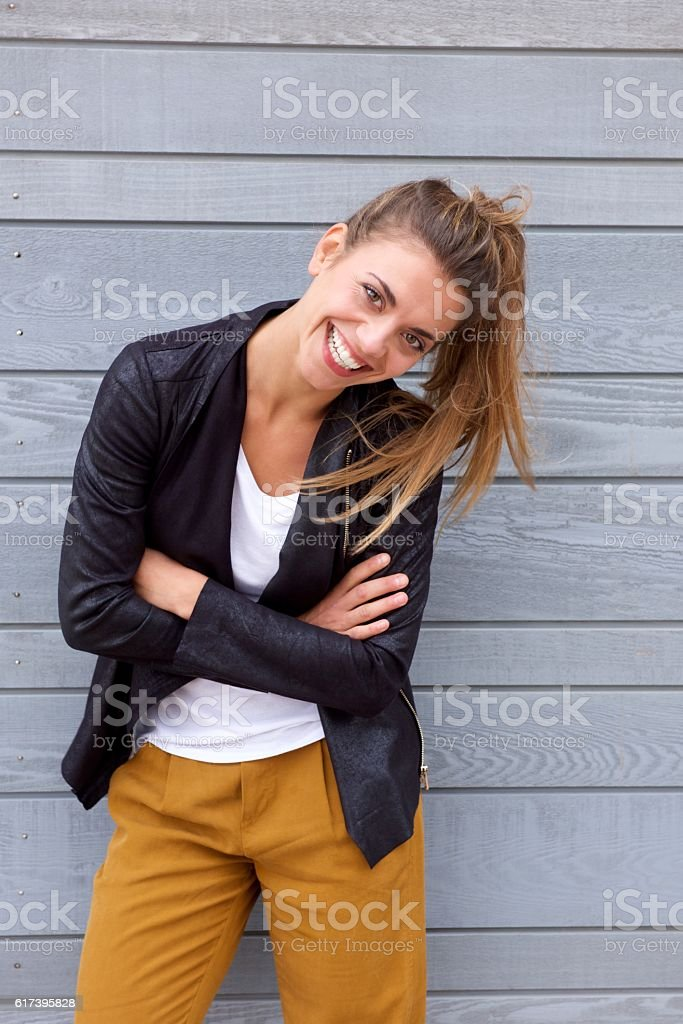 Laughing woman leaning with arms crossed stock photo