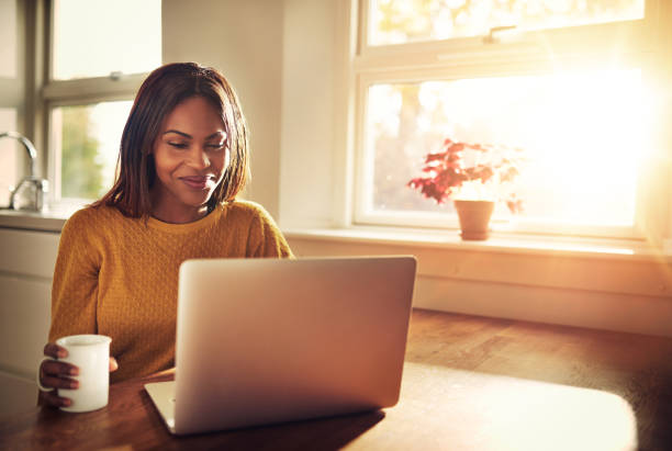 Laughing woman looking at laptop stock photo